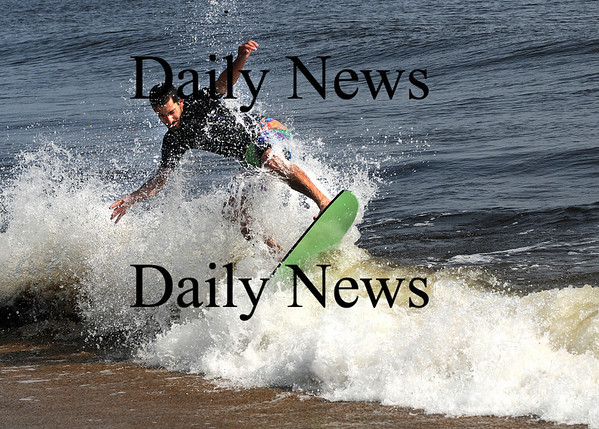 Newbury:Alan Robertson of Georgetown rides his skimboard through the surf on Plum Island on a unseasonably warm Sunday morning. Jim Vaiknoras/Staff photo