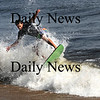Newbury:Alan Robertson of Georgetown rides his skimboard through the surf on Plum Island on a unseasonably warm Sunday morning. Jim Vaiknoras/Staff photo