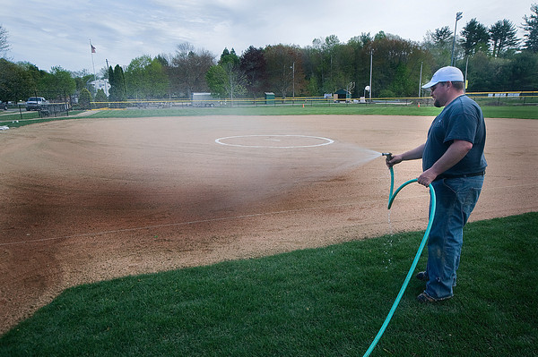 Newburyport: Landscaper Nate Buckley wets down the infield of the softball field at Pioneer Park in Newburyport Friday. The newly removated park will be on display as the season opens today. Jim Vaiknoras/Staff photo