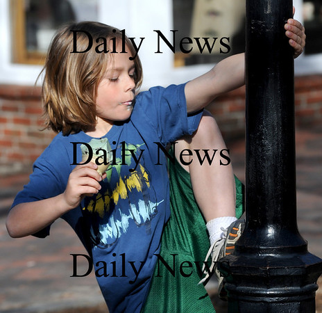 Newburyport: Max Tullgren , 8, of South Berwick Maine, eats an ice cream cone while climbing a lamppost on Inn Street in Newburyport Friday afternoon. Jim Vaiknoras/Staff photo