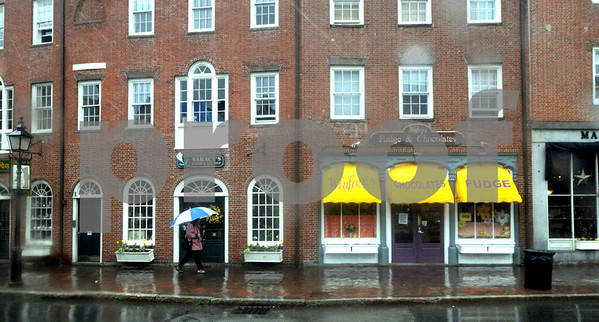 Newburyport: A woman keeps dry as she walks along  North Row in Market Square in Newburyport during the rain and snow Friday afternoon. Jim Vaiknoras/Staff photo