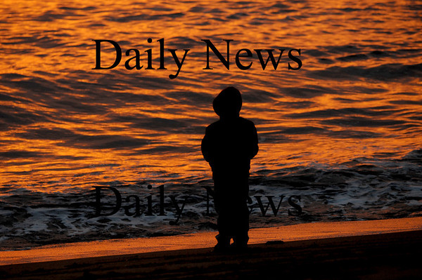 Newbury: Ben Reily, 6, watches the sunrise as members of the Central Congregational Church, The Belleville Congregational Church, and the First Parish Church Newbury gather to sing , pray and greet the Easter dawn on Plum Island Sunday. Jim Vaiknoras/Staff photo