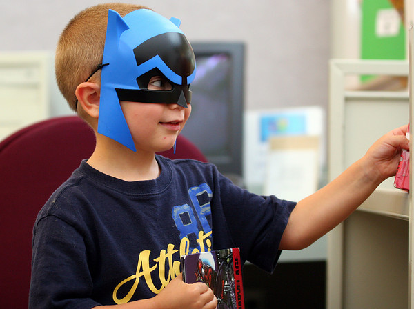 Byfield: A young dark knight, Brady Alantzas, 4, of Rowley, browses through some comic books at the Newbury Public Library Monday afternoon. Photo by Ben Laing/Staff Photo