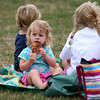 Newburyport: Phoebe Dooling, 1, of Byfield, snacks on a slice of pizza while watching her older brother at a track meet in Newburyport Tuesday evening. Photo by Ben Laing/Staff Photo