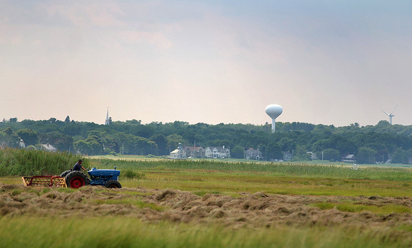 Newbury: A tractor rumbles throught the salt marsh off of the Old Point Road on Plum Island Monday afternoon as clouds begin to move in over Newburyport. Photo by Ben Laing/Staff Photo