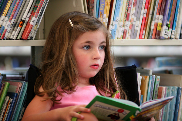 Byfield: Lily Westermann, 5, of Byfield, reads a book in the children's room at the Newbury Public Library Tuesday afternoon. Photo by Ben Laing/Staff Photo