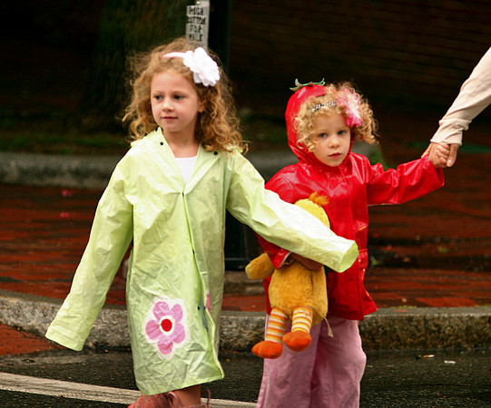 Newburyport: Hannah Gibeley, 6, left, and her sister, Amelia, 3, right, cross Merrimac Street in downtown Newburyport Monday afternoon while out shopping with their mom. The sisters were prepared for the rain, as the family made the trip downtown from Ipswich. Photo by Ben Laing/Staff Photo