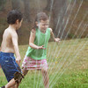 Amesbury: Zach Rome, left, and Linda Bullis, both 5, cool off in a lawn sprinkler at Amesbury Town Park yesterday morning. The youngsters are part of the summer program there which ends next week. Bryan Eaton/Staff Photo