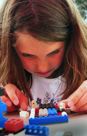 Amesbury: Amanda Bonaventura, 9, works on an old-fashioned home she's making out of Lego's. She was at the Amesbury Recreation's Summer Program which has its last day of the season today. Bryan Eaton/Staff Photo