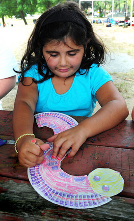 Amesbury: Olivia Nichols, 7, finishes coloring her eel she made out of paper plates at the Amesbury Recreation Department's Summer Program. Children cut out the plates in geometric shapes to make an eel or snakes and then color them in with their own design. Bryan Eaton/Staff Photo