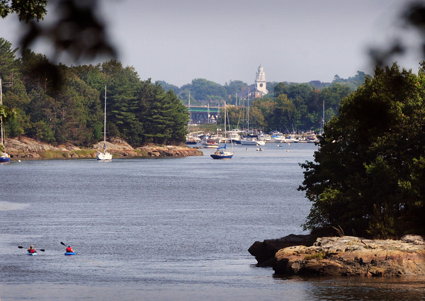 Amesbury: The Old South Church in Newburyport can be seen down the Merrimack River in a photo taken from Old Merrill Street in Amesbury, while kayakers go past Eagle Island to the right. Bryan Eaton/Staff Photo