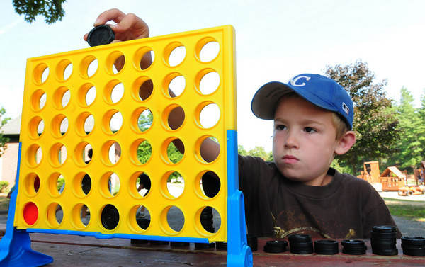 Amesbury: A look of intensity is on the face of Zachary Schneider, 7, as he plays Connect Four with his pal, Sam Heimlich, 6, at Amesbury Town Park on Wednesday afternoon. They were at the extended day Summer Program with the Amesbury Recreation Department. Bryan Eaton/Staff Photo