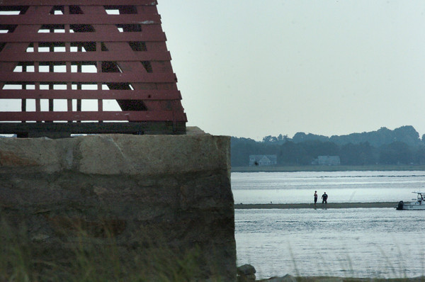 Salisbury: Two fisherman check out a sandbar past the navigational marker Ben Butler's Toothpick at Salisbury Beach State Reservation on Monday afternoon. Bryan Eaton/Staff Photo