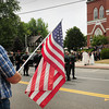 Amesbury: Marc Deschenes of Amesbury holds an American flag as the funeral procession of U.S. Army Ranger Sgt. Andrew C. Nicol leaves Holy Family Parish in Amesbury.  Deschenes is a friend of Nicol's relatives. Bryan Eaton/Staff Photo