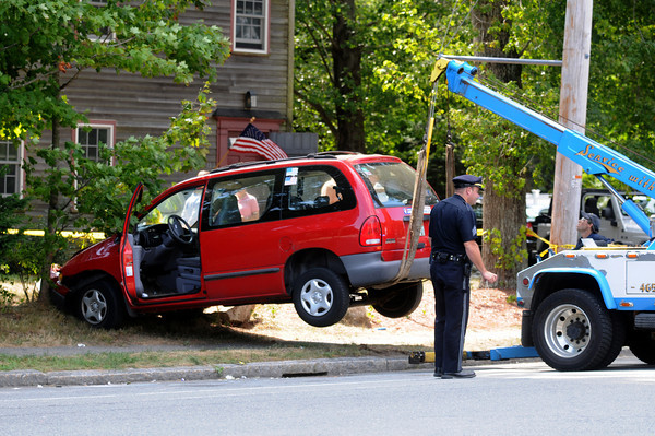 Newburyport: A tow truck lifts a car that was involed in a pedestrian accident on High Street in Newburyport Sunday afternoon. Jim Vaiknoras/Staff photo