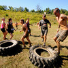 Amesbury: Runners do 15 standing jumps on a truck tire as a penalty for missing on the sprea toss in the Spartan Race at Amesbury Sports Park in Amesbury  Saturday. Jim Vaiknoras/Staff photo