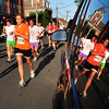 Newburyport: Runners of the 5K race head west on Water Street reflected in the window of an SUV. Bryan Eaton/Staff Photo