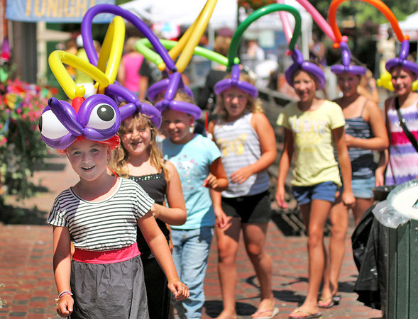 Newburyport: Ke'ala Ott, 10, of Newburyport leads a procession of her friends through Market Square Wednesday morning. Ke'ala was celebrating her 10th birthday with her friends, who all got balloon hats made by Mr. Dees, a local balloon artist. Photo by Ben Laing/Staff Photo