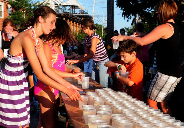 Newburyport: Volunteers grab cups of water to hand to runners along Water Street during yesterday's Yankee Homecoming road races. Bryan Eaton/Staff Photo
