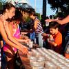 Newburyport: Volunteers grab cups of water to hand to runners along Water Street during yesterday's Yankee Homecoming road races. Bryan Eaton/Staff Photo