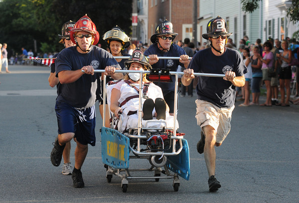 Newburyport: The Newbury Fire Dept entry makes it's way down Federal Street in the Yankee Homecoming Bed Race in Newburyport Thursday night. Jim Vaiknoras/Staff photo