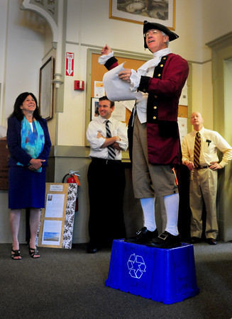 Newburyport: Newburyort Town Crier Charlie Cullen reads off Yankee Homecoming events at City Hall to Mayor Donna Holaday, left, and other employees yesterday morning. Bryan Eaton/Staff Photo