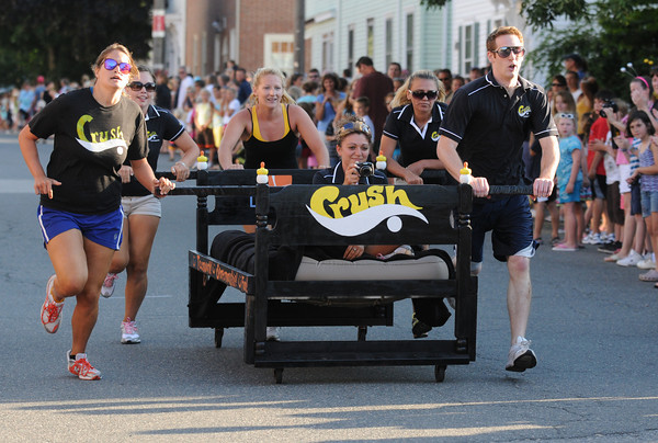 Newburyport: Crush Swimmers from Latitudes Gym runs down Federal Street in the Yankee Homecoming Bed Race in Newburyport Thursday night. Jim Vaiknoras/Staff photo