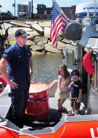 Newburyport: US Coast Guard Seaman Geoff Hill answers questions from a tour group aboard their response boat as Gianna Minichiello, 4, of Newburyport and Misha Drench, 4, of Melrose look around. Bryan Eaton/Staff Photo