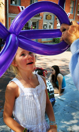Newburyport: McKenna Hallinan, 6, of Georgetown gets a Mickey Mouse balloon made by artist Mr. Dee on Inn Street. Bryan Eaton/Staff Photo