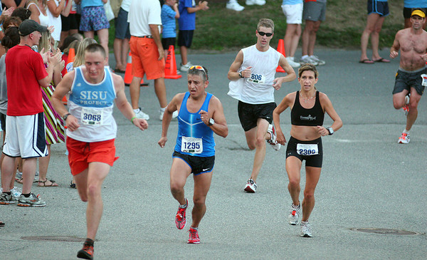 Newburyport: Racers push up the final hill at Newburyport High School during the 10 mile Yankee Homecoming Road Race Tuesday night. Photo by Ben Laing/Staff Photo