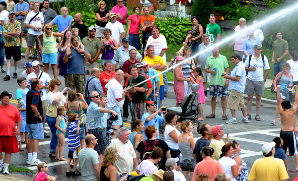 Newburyport: The Neptunes aim their hose down Pond Street at the annual muster at Old-Fashioned Sunday in Newburyport. Jim Vaiknoras/Staff photo