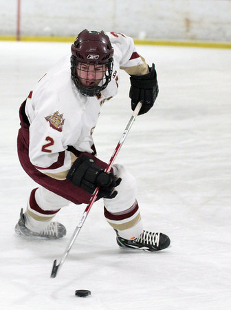Newburyport: Newburyport defenseman Billy Boudreau (2) scoops up a loose puck during Wednesday night's game against Amesbury. Photo by Ben Laing/Staff Photo