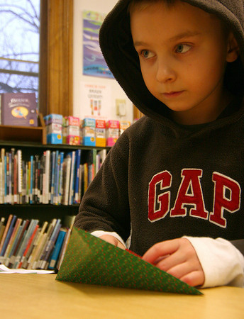 Amesbury: Hayden Ayotte, 9, of Amesbury, makes a oragami christmas decoration Monday afternoon at the Amesbury Public Library. Photo by Ben Laing/Staff Photo
