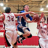 Amesbury: Georgetown's Tyler Wade (10) floats between Amesbury's Curran O'Connor (32) and Tyler Lay (20) on his way to the basket during Tuesday night's game. The two teams matched up in the second game of the 2nd annual Holiday Tournament doubleheader at Amesbury High School. Photo by Ben Laing/Staff Photo
