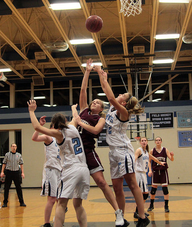 Byfield: Newburyport's Haley Johnson (11) lobs a ball over the outstreched arm of Triton's Jen Rock (32) during Wednesday night's game in Byfield. The Clippers won the Institution for Savings Holiday Tournament, defeating the Vikings 58-52. Photo by Ben Laing/Staff Photo