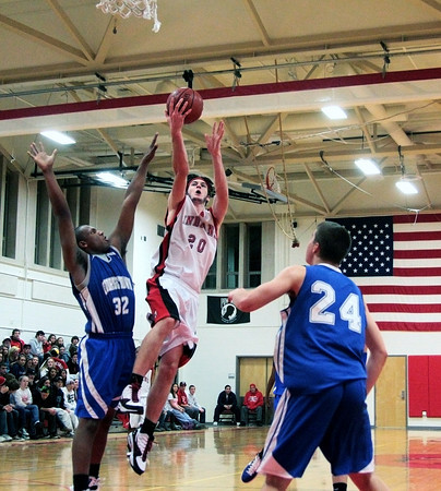 Amesbury: Amesbury's Tyler Lay (20) lays a ball in over Georgetown's Neph Carmona (32) during Tuesday night's game. The two teams matched up in the second game of the 2nd annual Holiday Tournament doubleheader at Amesbury High School. Photo by Ben Laing/Staff Photo