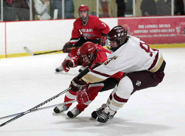 Newburyport: Newburyport's Kris Holmes (9) knocks the puck away from an Amesbury skater during Wednesday night's game at the Graf Rink. Photo by Ben Laing/Staff Photo