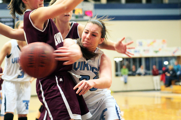 Byfield: Triton's Jessica Canning (30) dishes a pass around a Newburyport defender during Wednesday night's game in Byfield. The Clippers won the Institution for Savings Holiday Tournament, defeating the Vikings 58-52. Photo by Ben Laing/Staff Photo