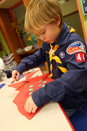 "Newbury: Derek Cotter, a second grader at Newbury Elementary, puts the finishing touches on his ""Christmas fish"" during Amy Merluzzi's art class Monday afternoon. Photo by Ben Laing/Staff Photo"