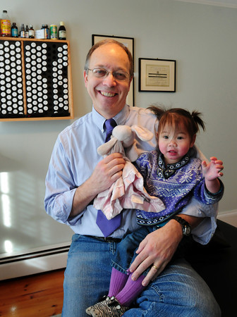 Newburyport: Dr. Dan Eyink, with daughter Phoebe Li, 19 months, specializes in diet and fitness. Bryan Eaton/Staff Photo
