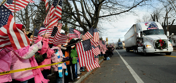 Rowley: Pine Grove School students in Rowley stood along Route 1A yesterday waving United States flags as a convoy of trucks rolled by carrying wreaths. The event was part of Wreaths Across America which lays wreaths on those buried at Arlington Cemetery. Bryan Eaton/Staff Photo