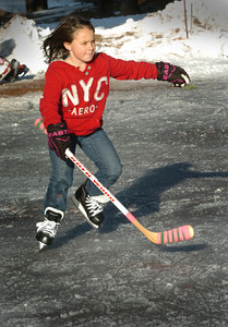 Amesbury: Millie Muraski, 8, of Amesbury moves along the ice at the skating rink at Amesbury Town Park with hockey stick in hand. She was there with her friends from the hockey team she's on. Bryan Eaton/Staff Photo