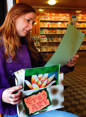 Newburyport: Katrina Svoboda of Newburyport takes a break from doing her crossword puzzle at Fowle's Coffeehouse to check out the offerings in the Free Art Box. Bryan Eaton/Staff Photo