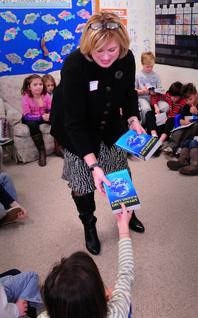 Newburyport: Lisa Sutton of Opportunity Works, hands out dictionaries to third-graders, while Geri Dorr, of Turning Point, out of view, talks to students. The two were part of over a dozen Rotarians who visited the Bresnahan School handing out the books. Bryan Eaton/Staff Photo