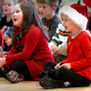 "Newburyport: Brown School kindergartners Adella Daigle, left, and Dylan Davis, both 5, sing the ""Dreidel Song"" at the school's Holiday Sing-a-long under the direction of Kathy Heywood on Wednesday morning. She also played with other children at Bresnahan School as she is music teacher at both. Bryan Eaton/Staff Photo"