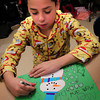 Amesbury: Joshua Fernandez, 9, creates a Christmas card for his parents in Cathy Berry's class at Amesbury Elementary School on Wednesday afternoon. The students had just watched the Polar Express wearing their pajamas, then enjoyed hot chocolate and candy canes then created whatever holiday card they chose. Bryan Eaton/Staff Photo