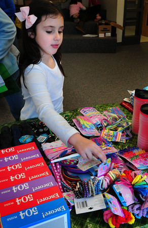 Salisbury: Kerrin Shea, 7, checks out some of the items to buy at the Holiday Shop at Salisbury Elementary School on Tuesday. The event, sponsored by the school's PTA, raises money for their enrichment program. Bryan Eaton/Staff Photo