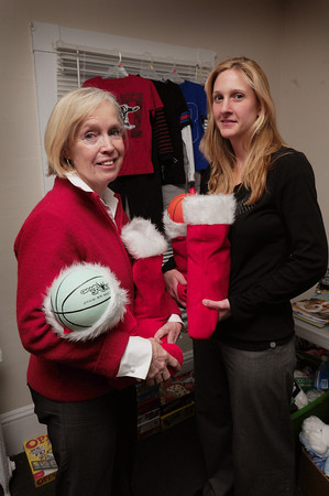 Salisbury: Deb Smith, left, and Tiffany Nigro of Pettengill House hold stockings stuffed for older children that were donated by a local high school hockey team. Bryan Eaton/Staff Photo