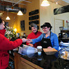Amesbury: Avery Ironhill gets some coffee at Ovedia Artisan Chocolates in Amesbury attended by owner Barbara Vogel, center, and Claudia Sanchez. The shop in downtown Amesbury posted better holiday business than last year. Bryan Eaton/Staff Photo