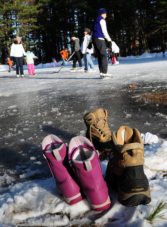 Amesbury: Boots sit on the side of the newly enlarged and busy ice skating rink at Amesbury Town Park on Thursday afternoon. Bryan Eaton/Staff Photo
